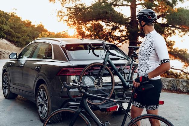 彼のクロスオーバー車のラックに彼の自転車をロードする男性サイクリスト
