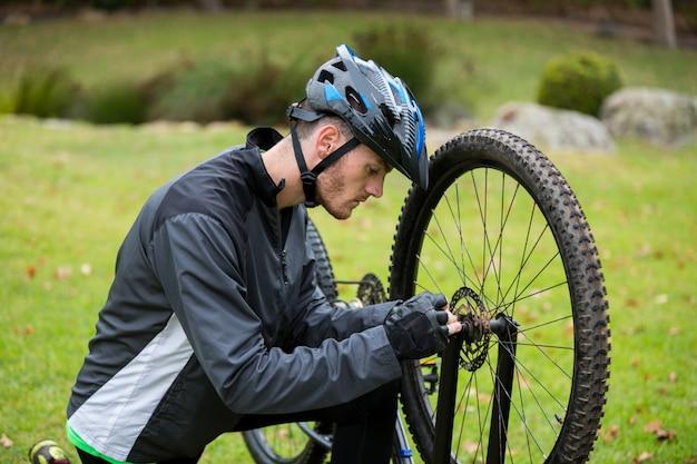 Мужской велосипедист ремонтирует свой горный велосипед