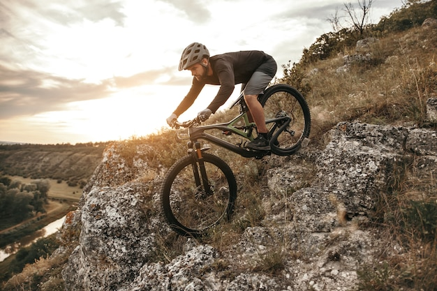 岩だらけの斜面でダウンヒルマウンテンバイクに乗る男性サイクリスト