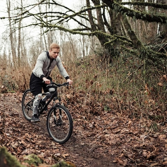 Male cyclist riding on forest trail
