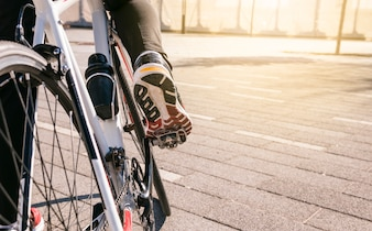 Male cyclist's foot on bicycle pedal riding bike at outdoors