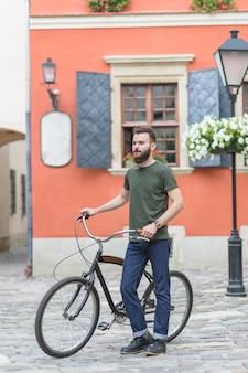 Мужской велосипедист, стоящий со своим велосипедом перед зданием