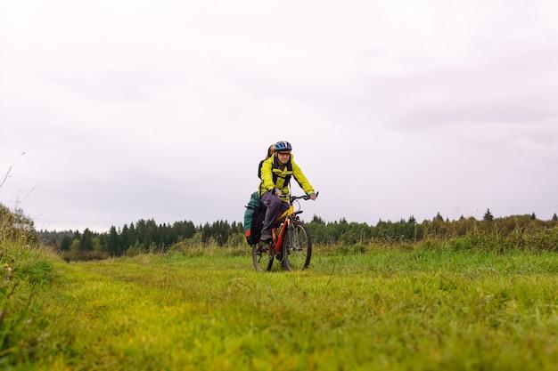 배낭과 안장 가방을 든 남성 자전거 여행자는 가을 초원을 타고