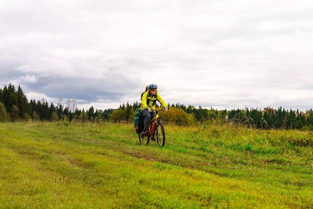 배낭과 랙 백을 든 남성 자전거 여행자는 자연 경관을 타고