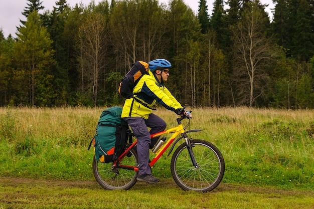 흐린 가을날 숲 가장자리를 따라 배낭을 메고 자전거를 탄 남성