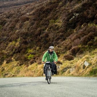 Велосипедист-мужчина в зеленой куртке поднимается на холм в уиклоу-маунтинс улыбается