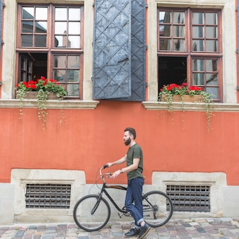 Male cyclist with his bicycle in front of building
