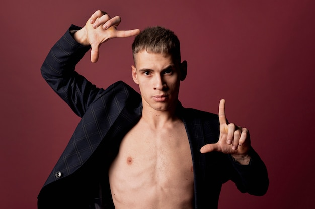 Male dancer creating frame with hands while posing in blazer without shirt