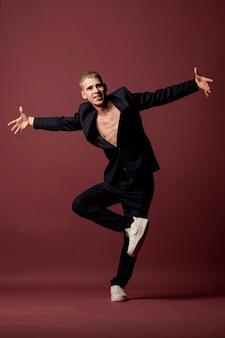 Танцовщица в кроссовках и костюме без рубашки перебирает ход