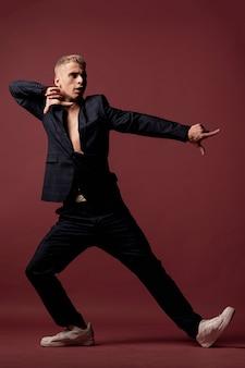 Мужской танцор в костюме и кроссовках позирует, указывая пальцем