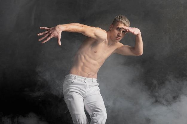 Мужской танцор позирует в дыму с джинсами