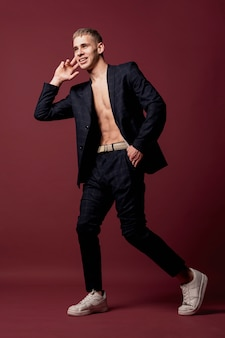 Male dancer posing in sneakers and suit without shirt