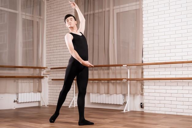 A male dancer rehearsing in a ballet class.