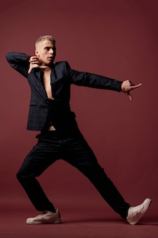 Male dancer in suit and sneakers posing while pointing fingers
