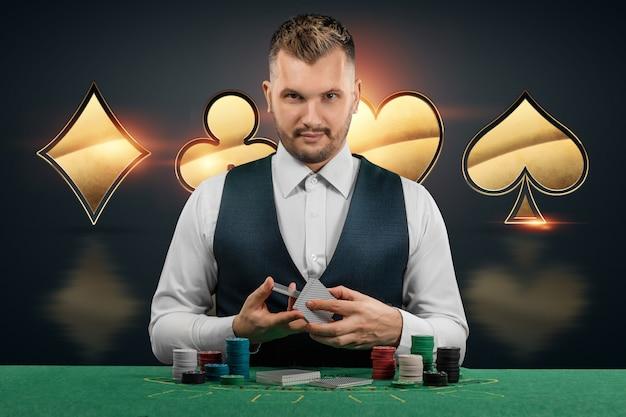 Мужчина-дилер в казино за столом. концепция казино, азартные игры, покер, фишки на зеленом столе казино.
