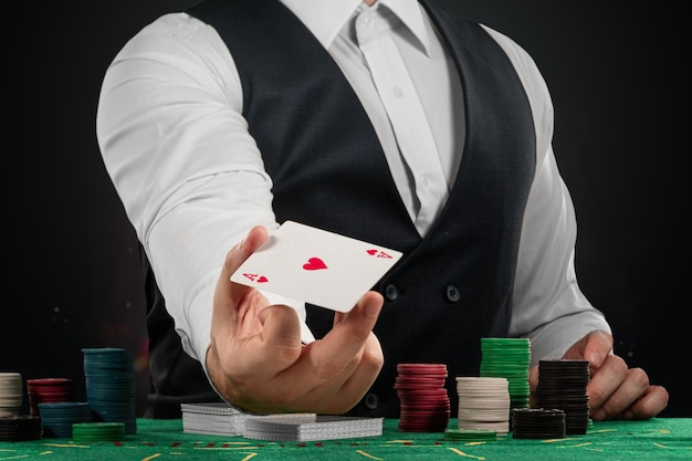 Male dealer at the casino at the table. casino concept, gambling, poker, chips on the green casino table.