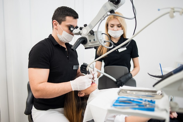 男性歯科医と歯科助手-歯科医院で顕微鏡、鏡、ドリルで患者の歯を治療する女性アシスタント。医学、歯科、医療のコンセプトです。