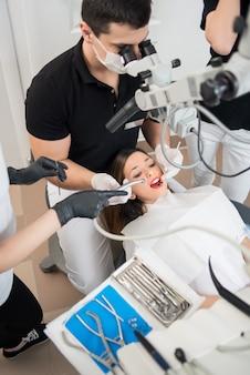 男性の歯科医と歯科ツールで患者の歯を治療する2人の女性アシスタント