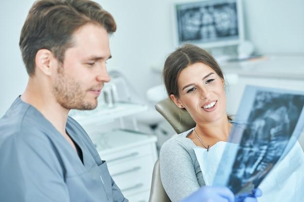 男性の歯科医と女性がx線の結果について歯科医院で話し合う