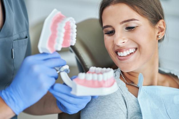 Мужчина-стоматолог и показывает челюсть женщине в стоматологической клинике
