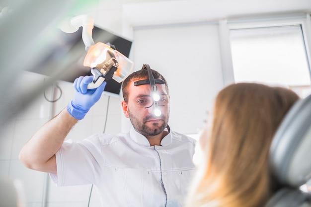 Male dentist examining female's teeth in clinic