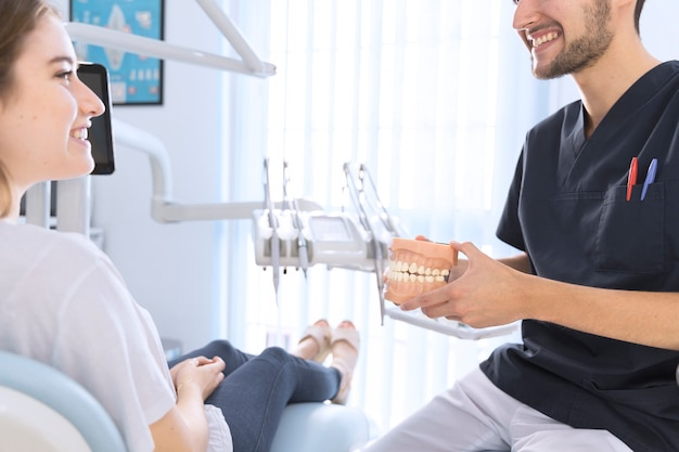 Male dentist explaining patient holding teeth model in clinic