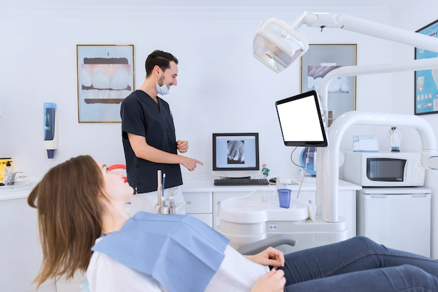 A male dentist explaining a teeth x-ray on screen to female patient lying on dentist chair
