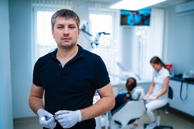 正面図のラテックス手袋の男性歯科医。フロントの背景に女性医師と患者。