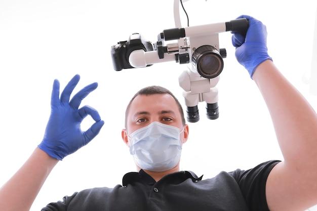 制服を着た男性歯科医、医療用マスク、カメラを見て指を見せているグラバーは大丈夫です。