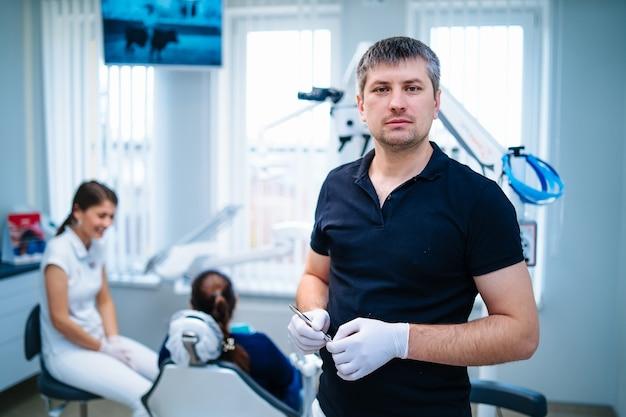 男性歯科医は現代の口腔病学クリニックで働いています。歯科医院の口腔病学器具。バックグラウンドで患者と女性の看護師。正面の医者。カメラを見てください。