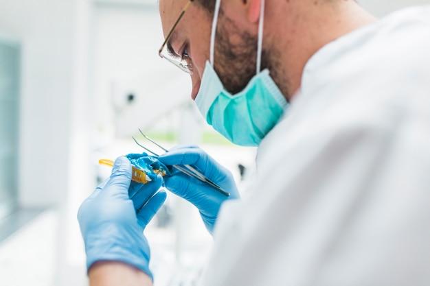 Male dentist preparing dental impression