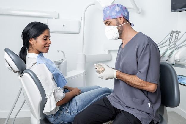 歯科医院の椅子に座っている女性患者に歯科用金型を示す男性歯科医