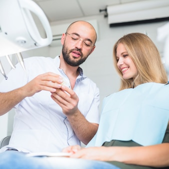 Male dentist showing dental jaw to happy female patient