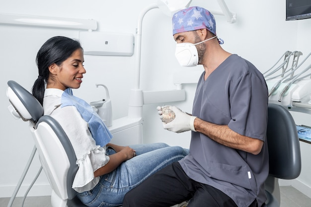 Male dentist showing a dental mould to a female patient sitting in a chair in a dental clinic