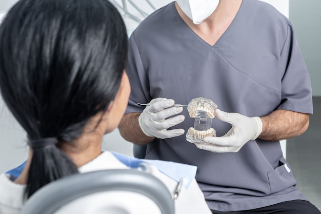 Male dentist showing an opened dental mould to a patient sitting in a chair in a dental clinic
