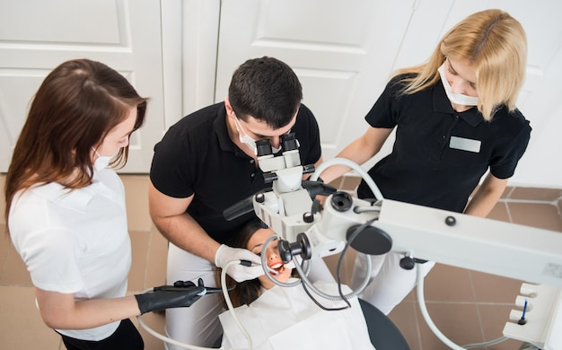 Male dentist and two female assistants checking up patient teeth with dental tools. dental equipment