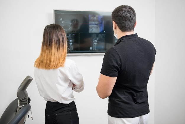 Male dentist with female patient looking at dental x-ray image on computer screen