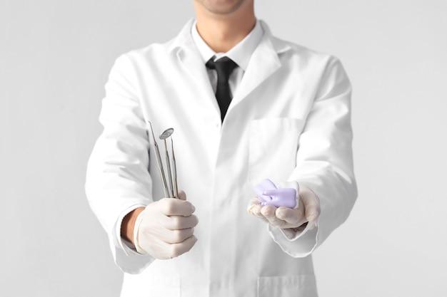 Стоматолог-мужчина с инструментами и пластиковыми зубами на светлой поверхности