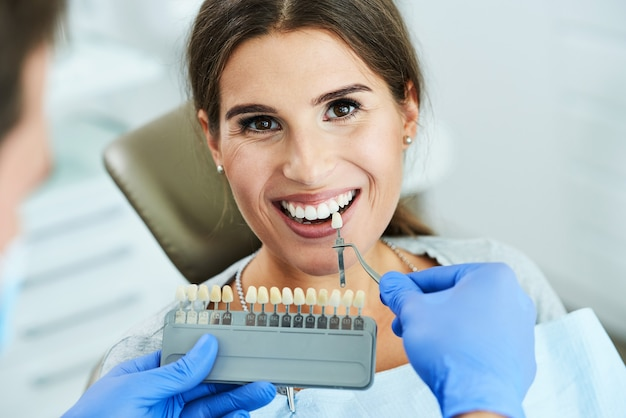 Male dentist and woman in dental clinic choosing implant shade