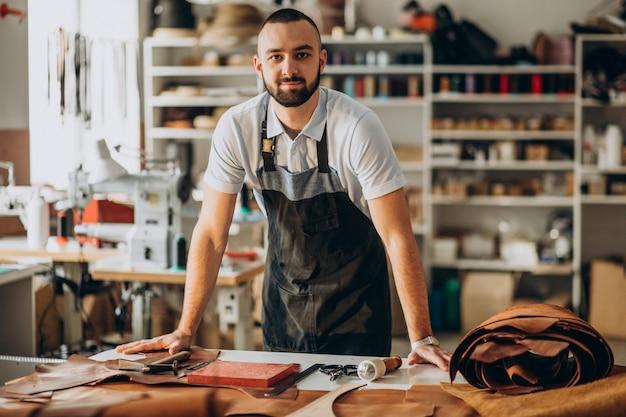 공장에서 일하는 남성 디자이너와 가죽 재단사