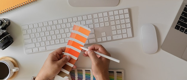 Male designer choosing colour on colour swatch while working with computer device on office desk
