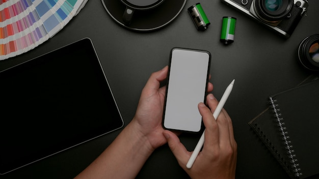 Male designer holding mock-up smartphone and working on digital tablet and supplies on dark office desk