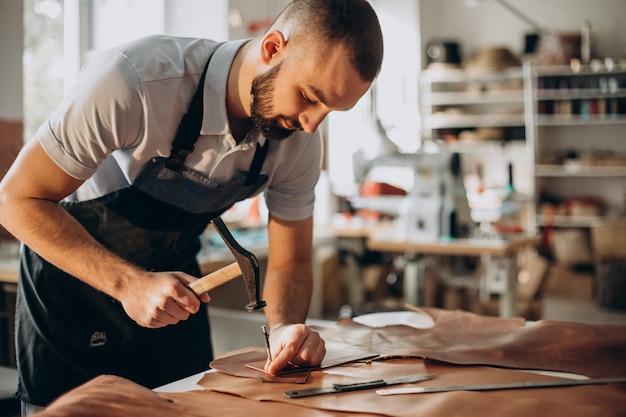 Designer maschio e sarto in pelle che lavora in una fabbrica