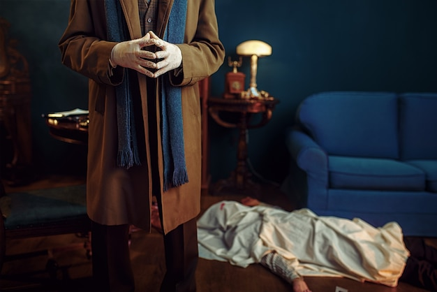 Male detective in gloves, victim under the cape at the crime scene, retro style. criminal investigation, inspector is working on a murder