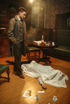 犯罪現場で岬の下の犠牲者を見ているコートの男性探偵