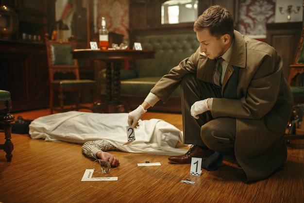 犯罪現場で証拠を見ている手袋をはめた男性探偵