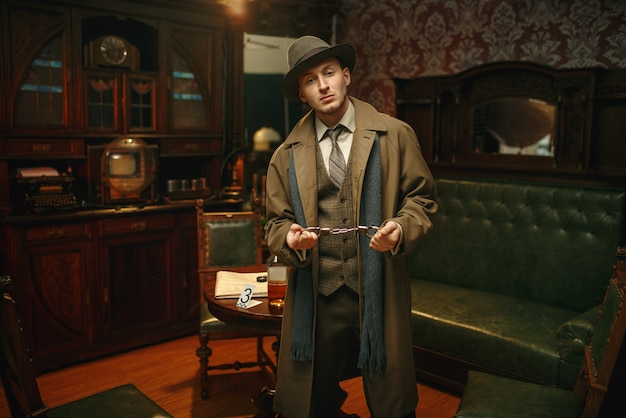 帽子とコートを着た男性刑事が犯罪現場で手錠を握っている