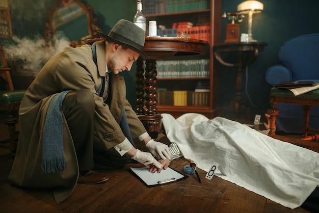 男性刑事は犯罪現場で死んだ男から指紋を取ります