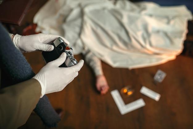 犯罪現場で写真カメラを持った男性刑事