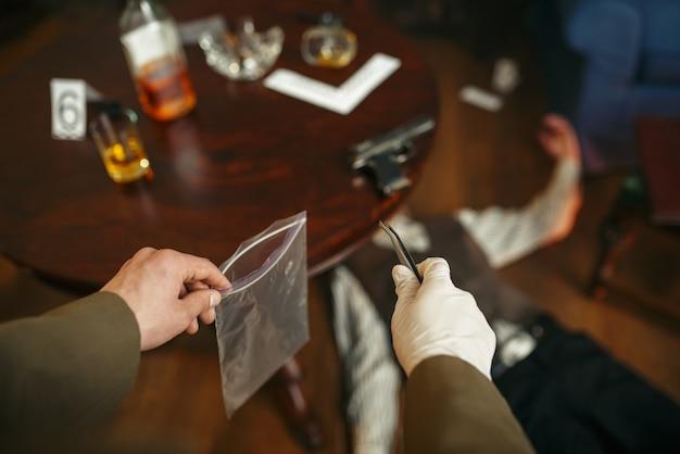 ピンセットを持った男性刑事が犯罪現場で証拠を探す